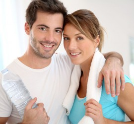 Portrait of smiling couple in fitness gym